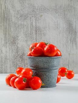 지저분한 벽과 흰색 표면에 미니 backet에 익은 젖은 토마토. 측면보기.