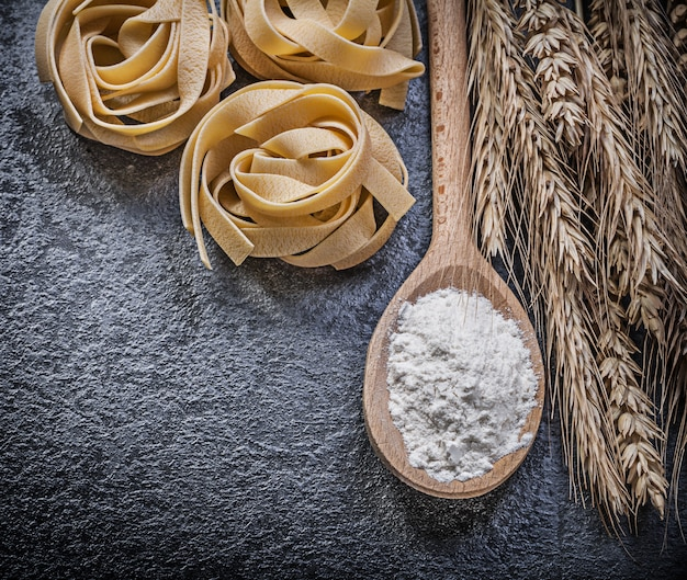 熟した小麦ライ麦の耳、木のスプーン、小麦粉、黒の表面に生パスタ
