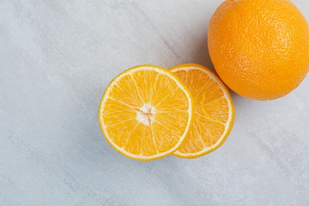 石の背景に熟した全体と半分のカットオレンジ。高品質の写真