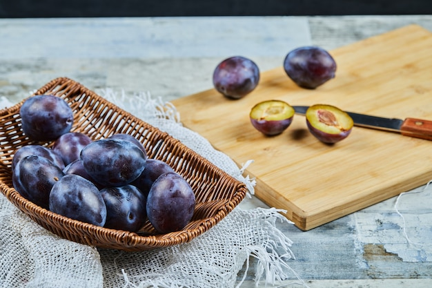 Ripe whole and half cut plums on wooden board.