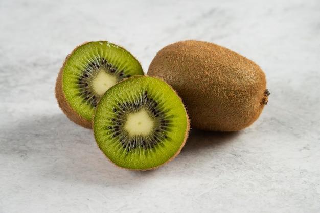 Спелые целые плоды киви и половина киви на белом.