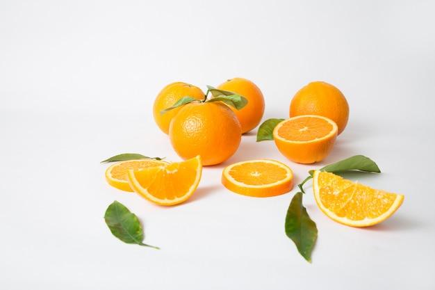 Спелые целые апельсины с зелеными листьями и нарезанными кусочками