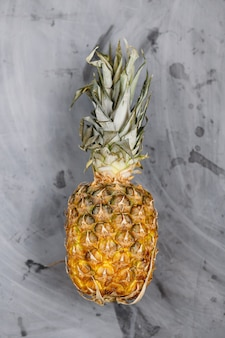 Ripe whole pineapple on grey concrete background.
