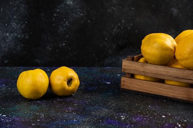 暗いテーブルの上の木製の箱にマルメロの果実全体を熟します。