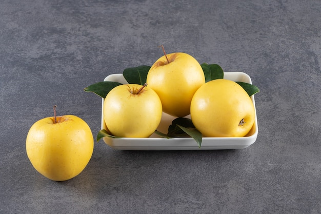 Ripe yellow apple with leaves placed on stone table .