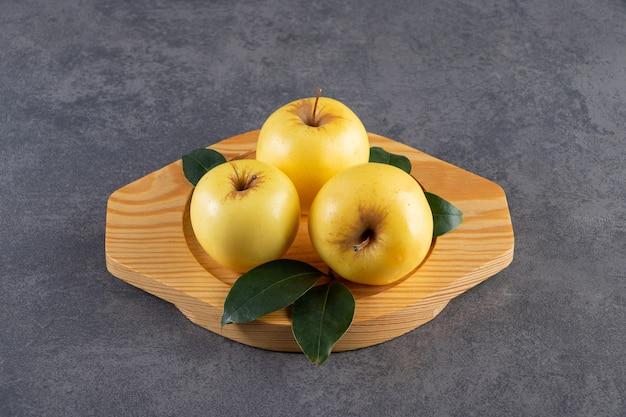 나무 접시에 녹색 잎으로 잘 익은 노란 사과.