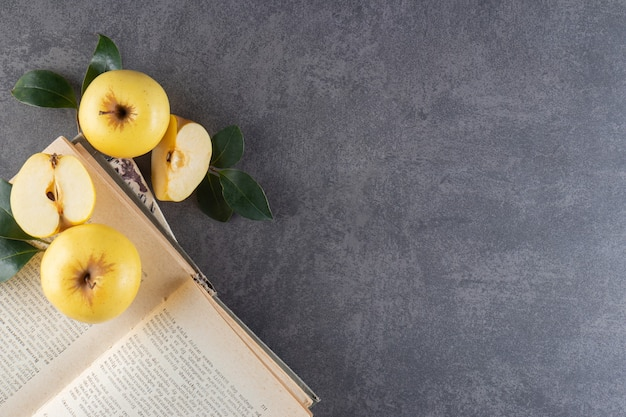 Ripe yellow apples with green leaves on top of book.