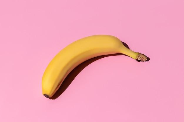 ピンクの背景に分離された熟した黄色のバナナ