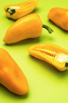 Ripe yellow bell pepper scattered on a green background. vegetarian food.