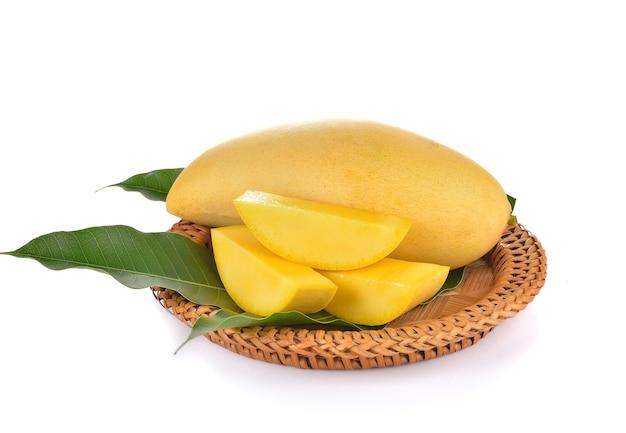 Спелое желтое манго с зелеными листьями на белом фоне