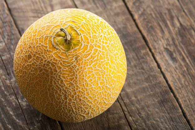 Ripe yellow melon on on wooden background