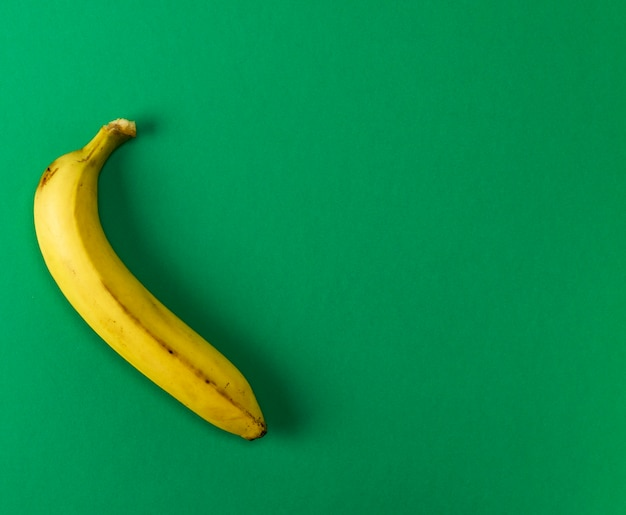Ripe yellow one banana on a green background