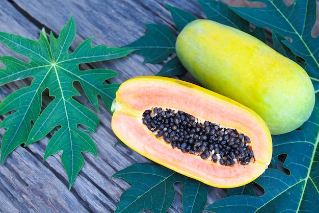 Ripe yellow papaya with green leaf on old wooden table background.