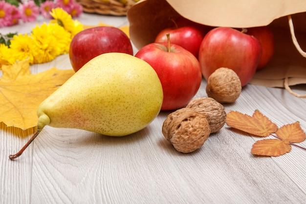 熟した黄色の洋ナシ、クルミ、紙袋の付いた赤いリンゴ、葉、木製の机の上の花。健康的な有機食品。秋のテーマ。