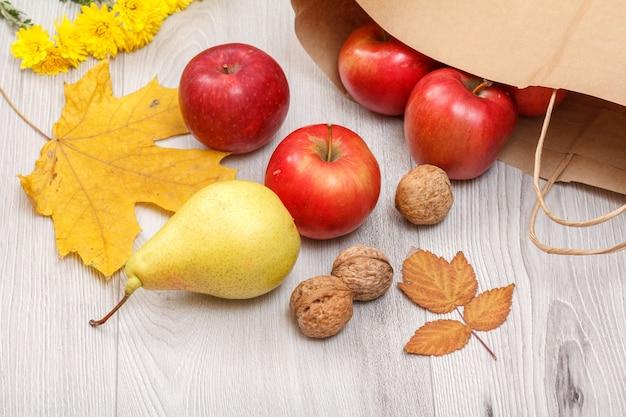 熟した黄色の洋ナシ、クルミ、紙袋の付いた赤いリンゴ、黄色の葉、木製の机の上の花。健康的な有機食品。秋のテーマ。上面図。