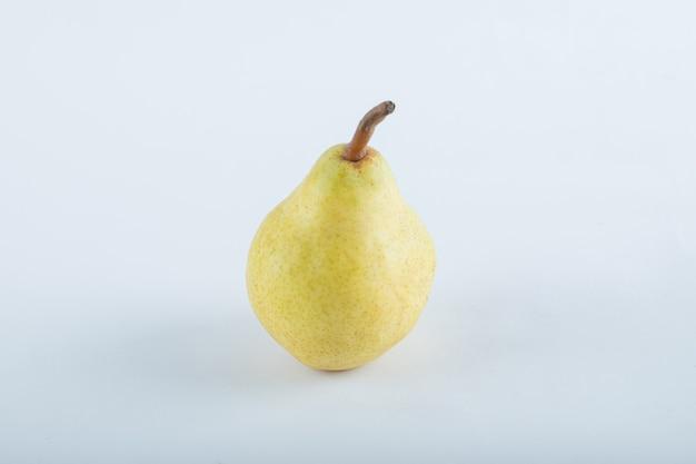 Pera gialla matura su bianco.