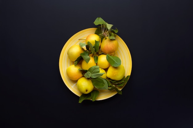 Ripe yellow pears with leaves on a yellow dish on dark