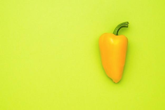 Спелый желтый перец на светло-зеленом фоне. вегетарианская пища.
