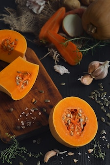 Ripe yellow pumpkin cut in half to make seasonal cream soup. layout of ingredients, vegetables and spices for making pumpkin soup on a black wooden table. top view