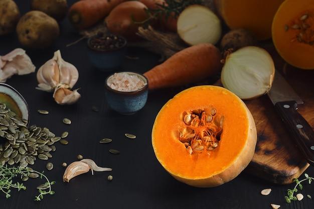 잘 익은 노란 호박을 반으로 잘라 제철 크림 스프를 만듭니다. 호박에 근접, 선택적 초점입니다. 검은 나무 테이블에 호박 수프를 만들기위한 재료, 야채 및 향신료