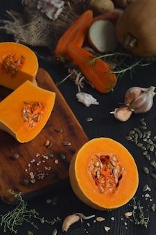 잘 익은 노란 호박을 반으로 잘라 제철 크림 스프를 만듭니다. 검은 나무 테이블에 호박 수프를 만들기위한 재료, 야채, 향신료의 레이아웃. 평면도