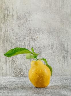 汚れた灰色の壁に熟した黄色のカリン。側面図。