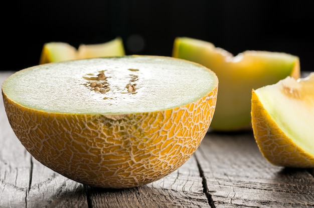 Ripe yellow sliced melon on wooden table