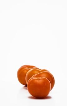 白い背景、クローズアップ、選択的な焦点に一列に熟した黄色いトマト。農場からのエコ野菜