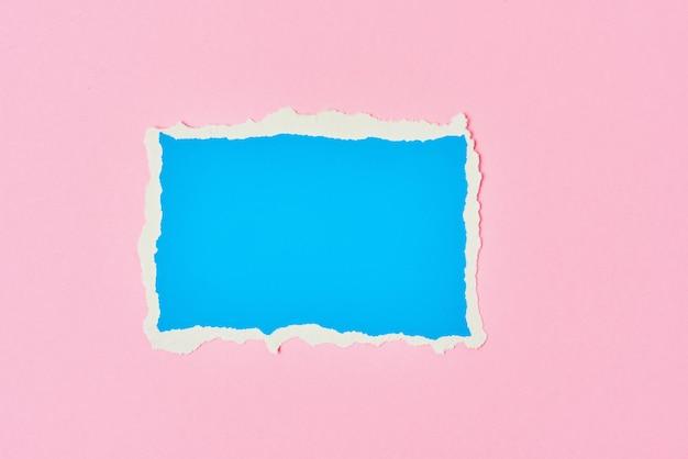 Сорванный лист сорванной края голубой бумаги на розовой предпосылке. шаблон с куском цветной бумаги