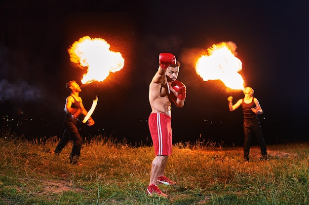 Ripped male boxer posing outdoors at night fire show performance
