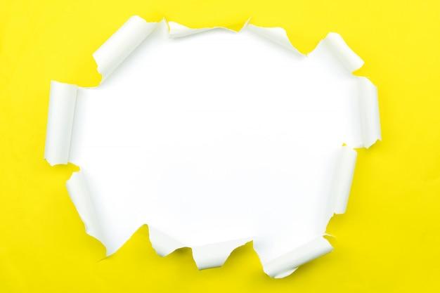 開いた紙をリッピング白で隔離される黄色の破れた紙。