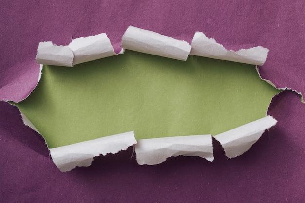 Разорванная или разорванная фиолетовая бумажная рамка с загнутыми краями и зеленым пространством для копий сзади в виде длинного овала
