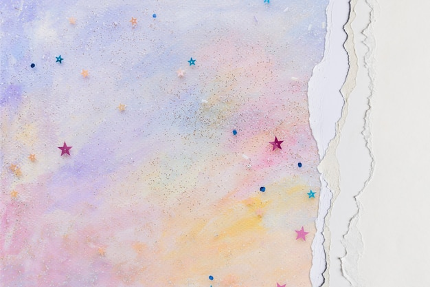 Ripped paper border in pink on handmade colorful pastel background