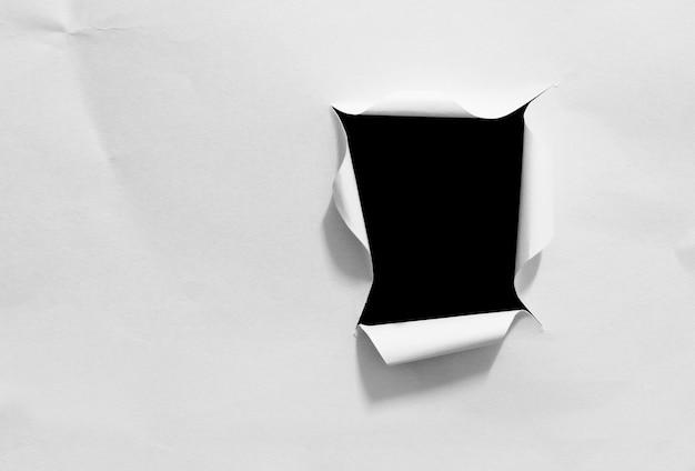 黒の背景に分離された破れた紙