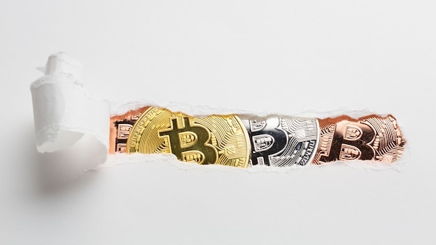 Ripped paper revealing bitcoin