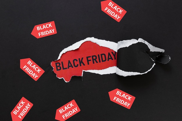 Ripped paper revealing black friday text with stickers