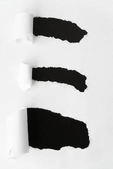 Ripped paper revealing black