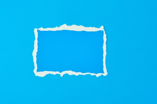 Ripped paper torn edge sheet on blue background. template with piece of color paper