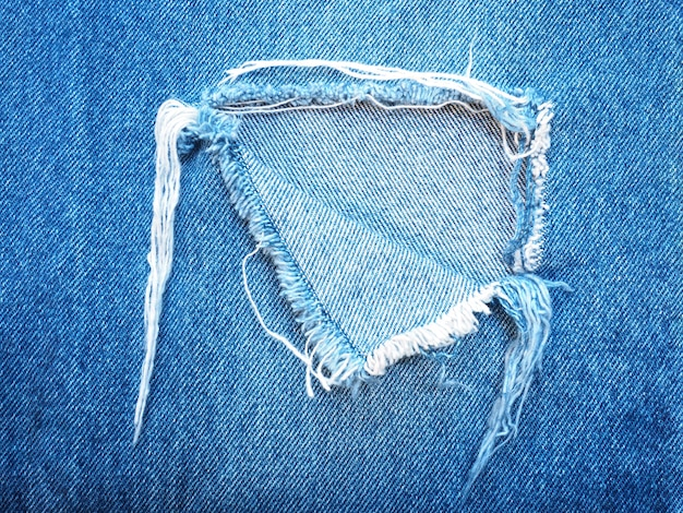 Ripped torn pattern of light blue jeans