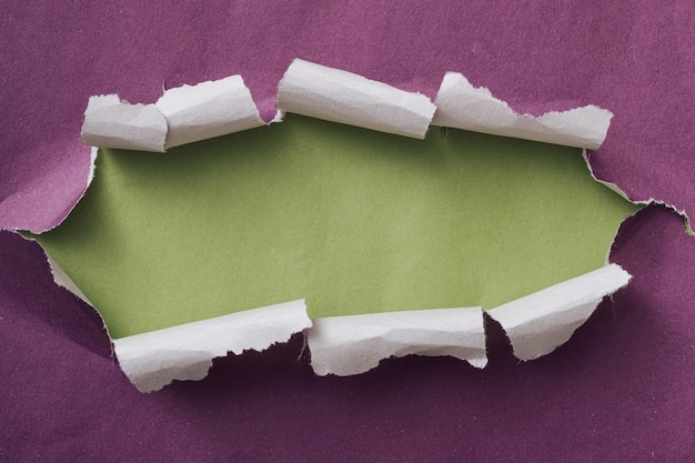 Ripped or torn purple paper frame with curling edges and green copy space revealed behind in a long oval shape