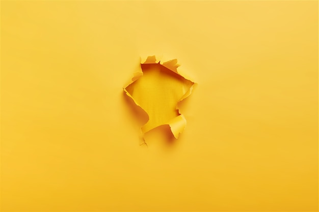 Ripped torn yellow paper with hole in center