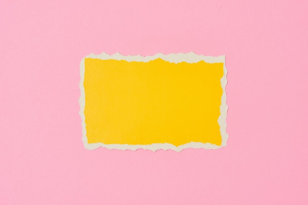 Ripped yellow paper torn edge sheet on pink. template with piece of color paper