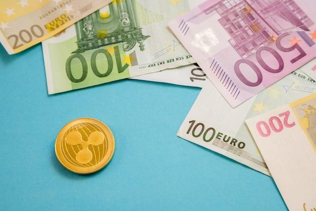 青い背景のユーロ紙幣の横にあるリップルコイン。デジタル通貨