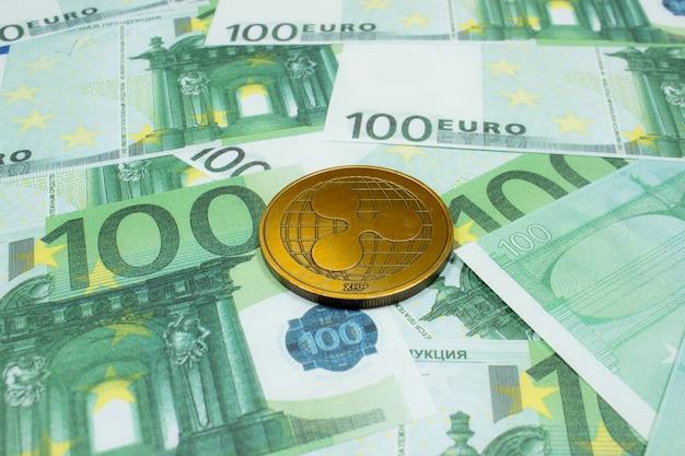 100유로 지폐에 있는 리플 동전이 닫힙니다. 암호화 xrp 코인.