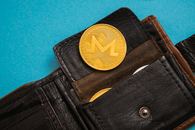 Ripple coin sticking out of leather wallet o blue background.