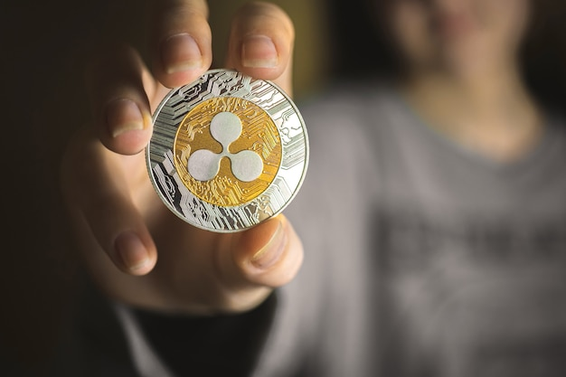 Ripple coin in young woman hand, close-up of crypto currency, business background photo