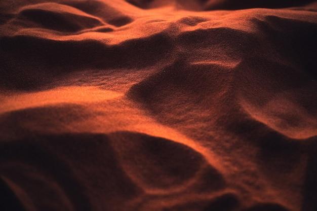 Рифленый светящийся песок пустыни на закате. естественный фон