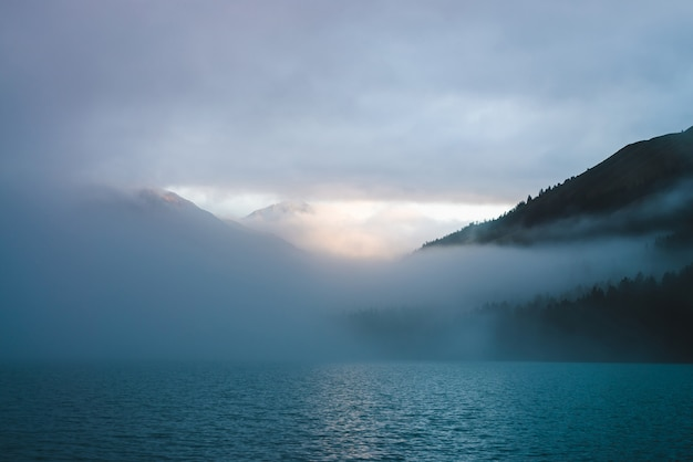 Рябь на поверхности горного озера в тумане в золотой час. солнце светит сквозь густые низкие облака в горах. солнечный след блестит на воде на рассвете. альпийский расслабляющий пейзаж с туманом в пастельных тонах.