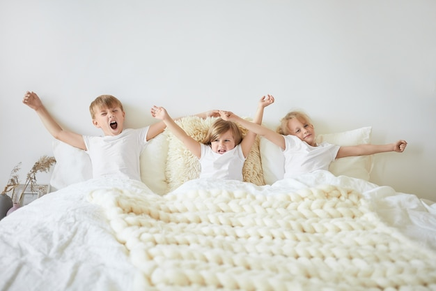Rise and shine. isolated horizontal shot of three siblings little sister and her two elder brothers wearing identical white t-shirts sitting on bed, stretching arms and yawning in the morning