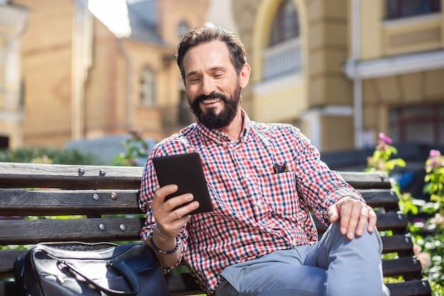 気分を盛り上げましょう。ベンチで電子書籍を読んで楽しいハンサムな男
